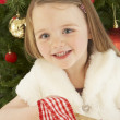 Young Girl Holding Christmas Present In Front Of Christmas Tree - Photo