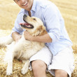 Man Sitting With Dog On Straw Bales In Harvested Field — Stock Photo #4841093