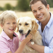 Stock Photo: father and son sitting with dog on straw bales in harvested fiel