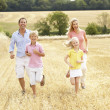Family Running Together Through Summer Harvested Field — Stock Photo #4841125