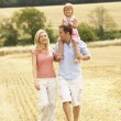 Family Walking Together Through Summer Harvested Field — Stock Photo #4841139