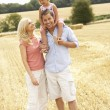 Family Walking Together Through Summer Harvested Field — Stock Photo #4841140