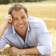 Portrait Of Man Laying In Summer Harvested Field — Stock Photo #4841186