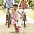 Family Cycling In Countryside Wearing Safety Helmets — Stock Photo #4841198