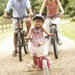Family Cycling In Countryside Wearing Safety Helmets — Stockfoto