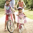 Family Cycling In Countryside Wearing Safety Helmets — Stock Photo #4841204