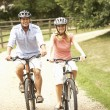Stock Photo: Couple Cycling In Countryside Wearing Safety Helmets