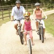 Family Cycling In Countryside Wearing Safety Helmets — Stock Photo #4841210