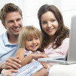 Family Sitting On Sofa Using Laptop At Home - Stock Photo