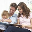 Family Sitting On Sofa Reading Book At Home — Stock Photo #4841261
