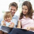 Stock Photo: Family Sitting On SofReading Book At Home