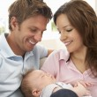 Close Up Of Parents Cuddling Newborn Baby Boy At Home - Foto Stock