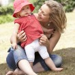 Mother And Daughter Playing Together In Garden At Home - Foto de Stock  