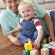 Father And Son Playing With Coloured Blocks At Home - Foto Stock