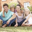 Family Sitting In Garden Together - Foto Stock