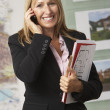 Young business woman talking on cellphone and holding document with smiling - Stock Photo