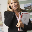 Young business woman talking on cellphone and holding document with smiling — Stock Photo #4841433