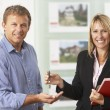 Stock Photo: Female Estate Handing Over Keys Of New Home To Client