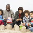 Young Family Building Sandcastle On Beach Holiday — Stock Photo