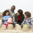 Young Family Building Sandcastle On Beach Holiday - Stock Photo