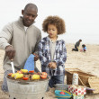 Young Family Enjoying Barbeque On Beach — Foto Stock