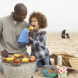 Young Family Enjoying Barbeque On Beach — Stockfoto