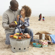 young family enjoying barbeque on beach — Stock Photo
