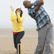 Royalty-Free Stock Photo: Young Couple Playing Cricket On Autumn Beach Holiday