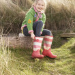 Young Girl Putting On Wellington Boots - Foto Stock