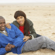Young Couple Relaxing On Winter Beach Holiday — Stockfoto