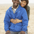 Young Couple Relaxing On Winter Beach Holiday — Stock Photo