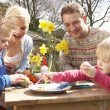 Family Decorating Easter Eggs On Table Outdoors — Lizenzfreies Foto