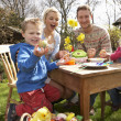 Family Decorating Easter Eggs On Table Outdoors — Stock Photo