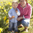 Stock Photo: Mother And Son On Easter Egg Hunt In Daffodil Field