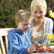Mother And Son Decorating Easter Eggs On Table Outdoors — Stock Photo