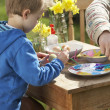 Father And Son Decorating Easter Eggs On Table Outdoors - Stock Photo
