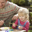 Father And Daughter Decorating Easter Eggs On Table Outdoors — Stock Photo