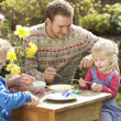 Royalty-Free Stock Photo: Family Decorating Easter Eggs On Table Outdoors
