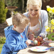 Mother And Son Decorating Easter Eggs On Table Outdoors - Stock Photo