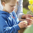 Mother And Children Decorating Easter Eggs On Table Outdoors - Stock Photo
