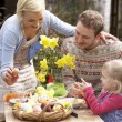 Family Decorating Easter Eggs On Table Outdoors — Stock Photo #4841887