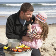 Stock Photo: Father And Daughter Having Barbeque On Winter Beach
