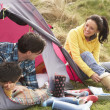Young Family Relaxing Inside Tent On Camping Holiday — Stock Photo #4842030
