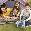 Young Family Relaxing Inside Tent On Camping Holiday — Stock Photo #4842039