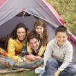 Young Family Relaxing Inside Tent On Camping Holiday — Stock Photo #4842041