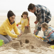 Family Building Sandcastle On Winter Beach - Stock Photo