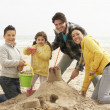 Stock Photo: Family Building Sandcastle On Winter Beach