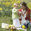 Mother And Daughter In Daffodil Field With Decorated Easter Eggs - Foto Stock