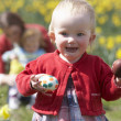 Mother And Children In Daffodil Field With Decorated Easter Eggs - Stock Photo