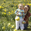 Mother And Daughter In Daffodil Field With Decorated Easter Eggs - Stockfoto